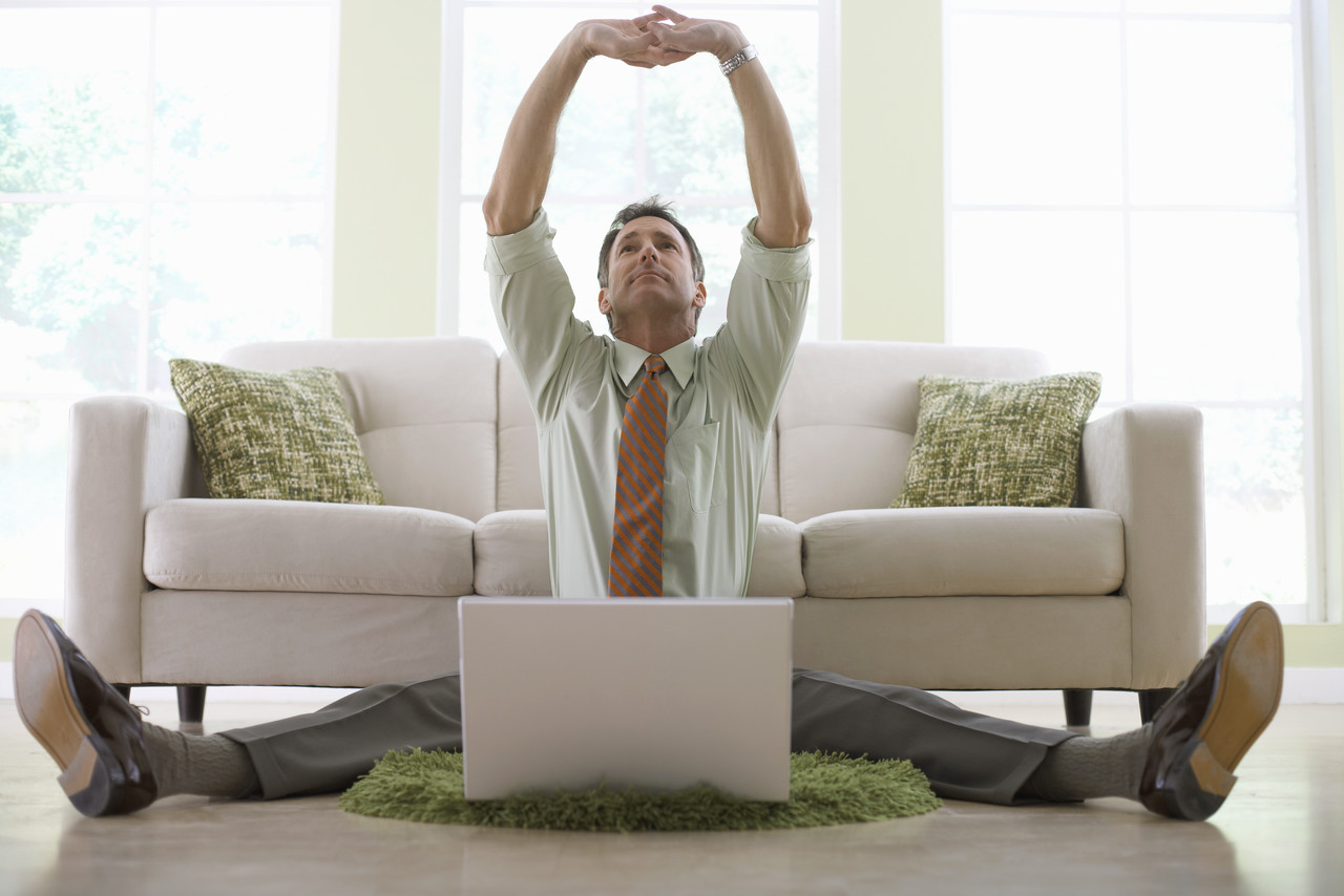 Businessman Stretching While Working on His Laptop